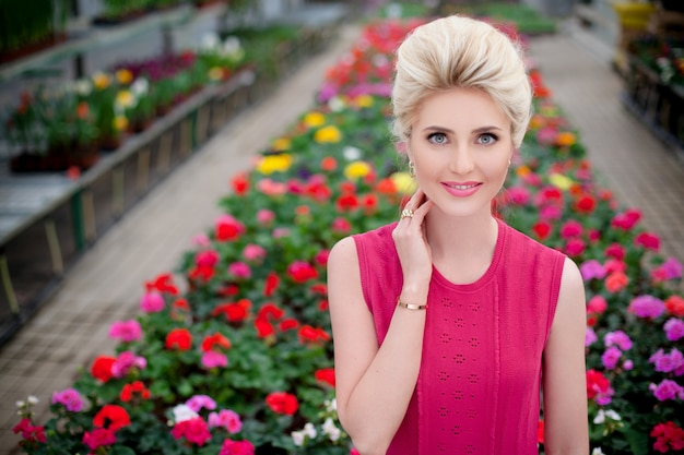 Frontal portrait of a beautiful blonde girl having a flower garden on the background