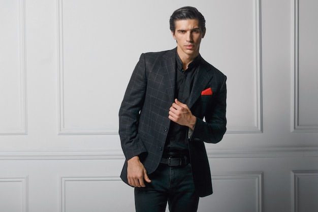 Frontal portrait of confident young man in black elegant suit with red silk scarf in pocket, over white background.