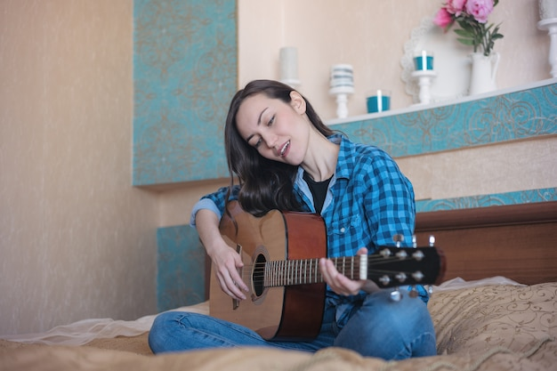 Frontal portrait of a girl with an acoustic guitar on the bed