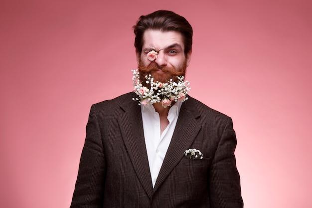 濃いピンクの背景に分離された、ひげの花とスーツを着た面白いファッショナブルなひげを生やした男の正面の肖像画。