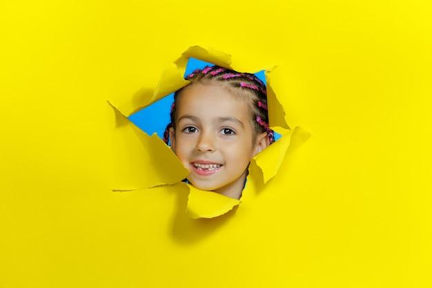 노란 종이에 구멍에서 찾고 작은 웃는 귀여운 소녀의 정면 초상화. 가로보기. 공간을 복사하십시오.