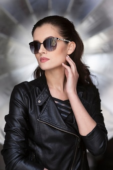 Фронтальный портрет сексуальной модной брюнетки женской модели, одетой в черную кожаную куртку и стильные солнцезащитные очки.