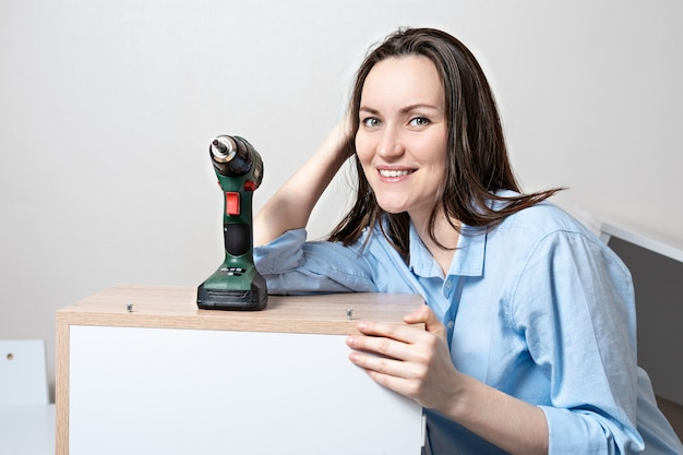 Frontal portrait of young smiling european woman with electric screwdriver leaning on the assembled table
