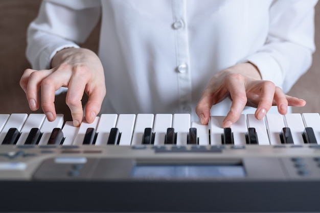 Frontal view of female hands practiced playing the synthesizer