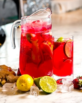 Frontal view invigorating lemonade with lemon lime strawberries and ginger