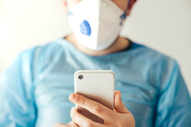 Frontal view of unknown woman wearing protection mask and blue suit using the phone