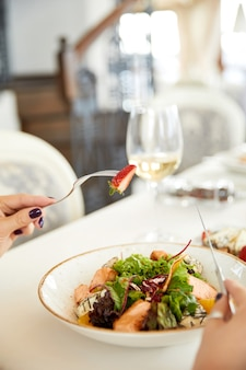 Frontview of a fresh salad on the foreground and a glass with a white wine