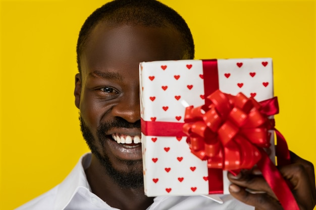 Frontview of laughing bearded young afroamerican guy with one present in hand that closed half of face in white shirt