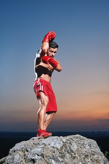 Frontview of muscular male boxer practising skills outdors