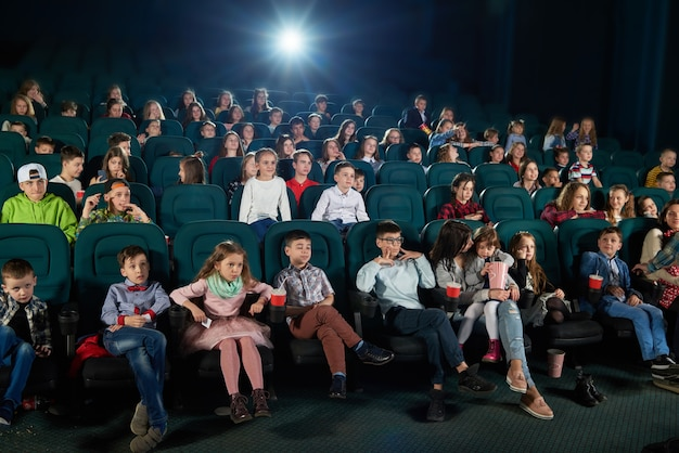 Frontview of people watching movie in the cinema hall.