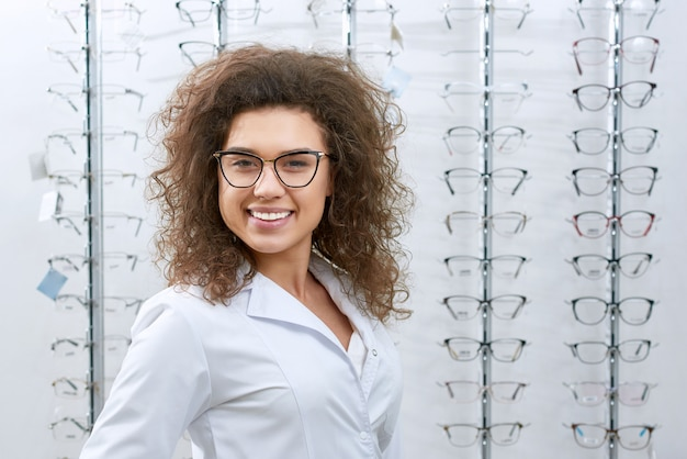 Frontview of smiling curly ophthalmologist posing near stand with eyeglasses.
