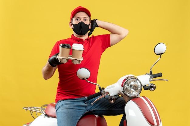 Frontview del fattorino sorpreso che indossa guanti uniformi e cappello in mascherina medica che si siede sullo scooter che mostra gli ordini
