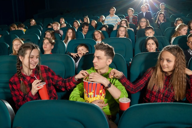 Frontview of three friends eating popcorn by watching movie.