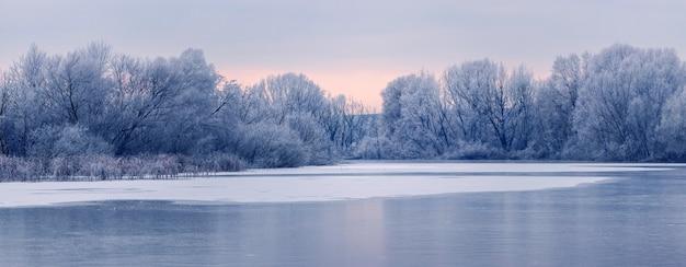 日の出の朝、氷に覆われた川のほとりにある霜に覆われた木々