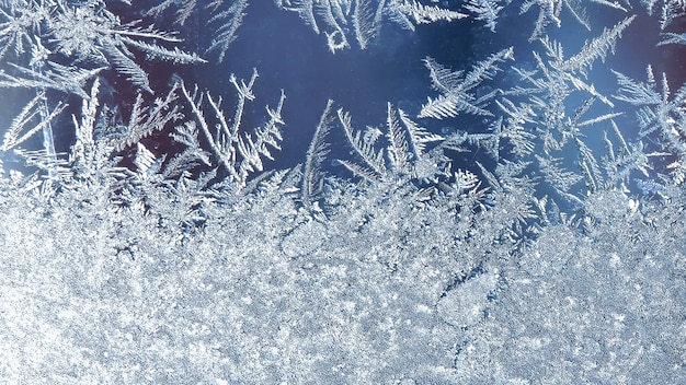 Морозные узоры на окне, фон из инея. морозный узор на зимнем оконном стекле