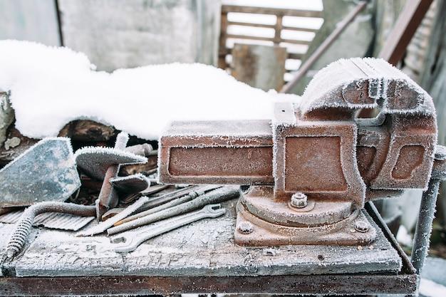 외부 작업장에 서리로 덥은 바이스 도구. 겨울에 도구를 외부에 두었습니다. 추위, 초기 서리, 호어 컨셉