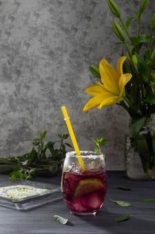 Морозный напиток со льдом и дольками лимона на сером столе и вазе с желтыми цветами