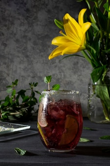Frosty drink with ice and lemon slices on a gray table and a vase with yellow flowers