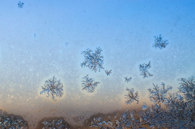 Frosty frozen patterns from the ice on the window in winter