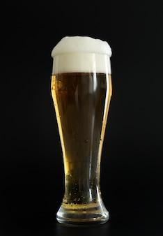 검은 배경에 거품이 있는 차가운 황금 맥주 한 잔. 파티, 휴일, 옥토버페스트 또는 성 패트릭의 날에 음주
