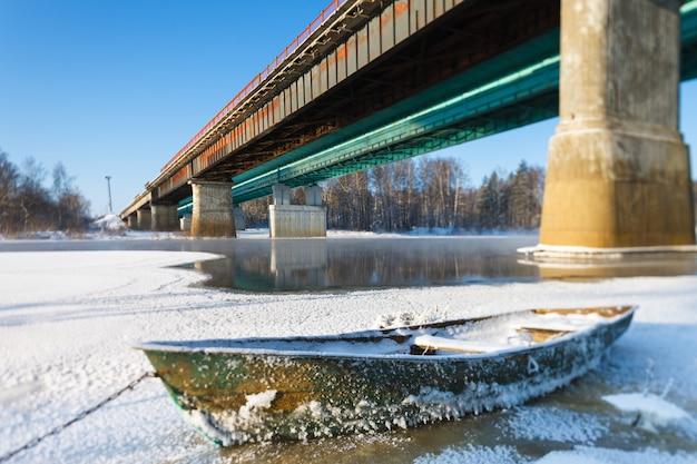 Frosty landscape boat on frozen river crossing