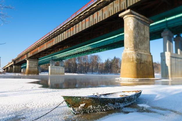 Морозный пейзаж ледяной лодки на фоне моста через реку