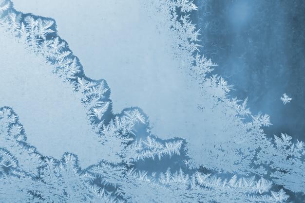 Морозные узоры на крупном плане оконного стекла. натуральные текстуры и фоны. ледяной узор на замороженном