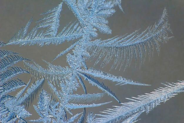 Морозные узоры на крупном плане оконного стекла. натуральные текстуры и текстуры. ледяной узор на замороженном