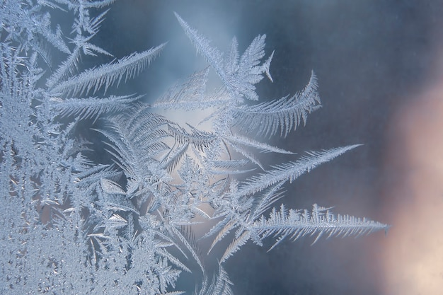 Frosty patterns on the window glass closeup. natural textures and backgrounds.