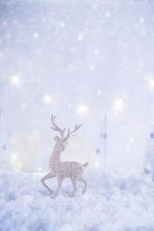 Морозная зимняя страна чудес с игрушечными оленями, снегопадом и волшебными огоньками. рождественские поздравления концепция