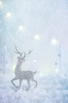 Frosty winter wonderland with toy deer, snowfall and magic lights.  christmas greetings concept
