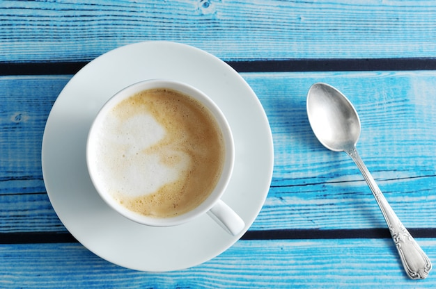 Frothy coffee with cappuccino in a white mug on a blue wooden background