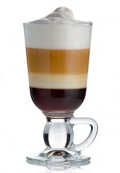 Frothy, layered cappuccino in a clear glass mug with cinnamon sprinkled