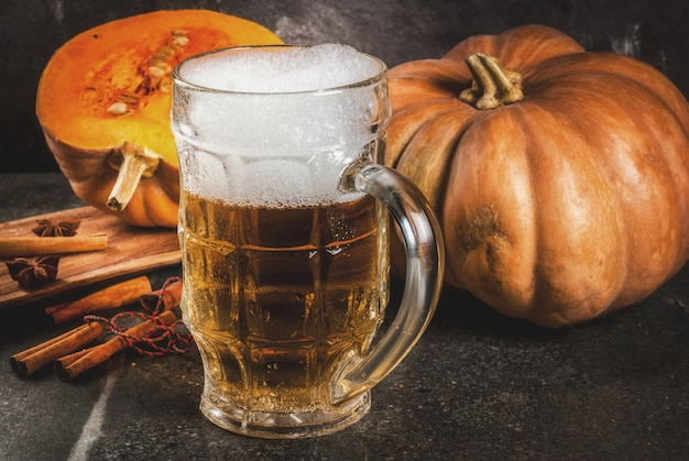 Frothy spicy pumpkin ale or beer in glass mug, on black background