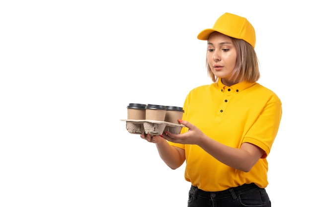 A frotn view female courier in yellow cap yellow shirt and black jeans holding cups of coffee