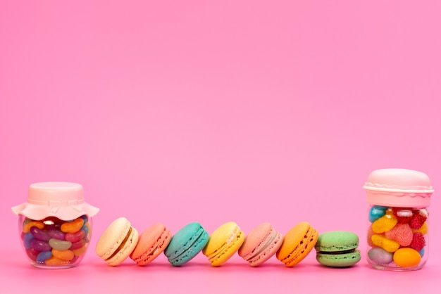 A frotn view french macarons along with multicolored candies inside cans on pink