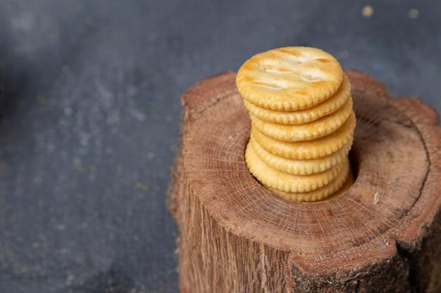 木と灰色の背景のクッキービスケットクラッカーの写真に丸い甘いクッキーfrotnビュー
