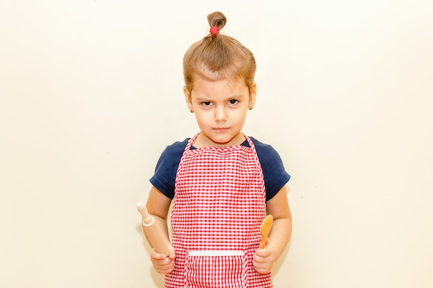 Frowned little girl with chef apron holding wooden rolling pin and a spoon on beige background