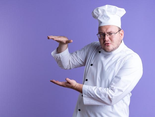 眉をひそめている大人の男性料理人シェフの制服を着て、正面を見て、コピースペースで紫色の壁に分離されたサイズのジェスチャーを示す縦断ビューで眼鏡をかけている