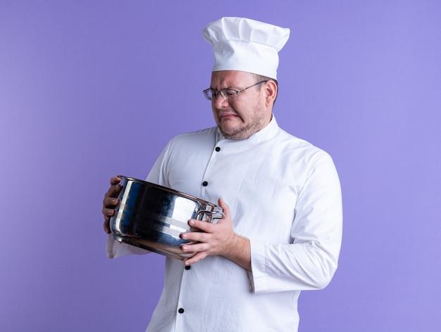 Accigliato maschio adulto cuoco indossando l'uniforme dello chef e occhiali tenendo e guardando all'interno del vaso isolato su parete viola