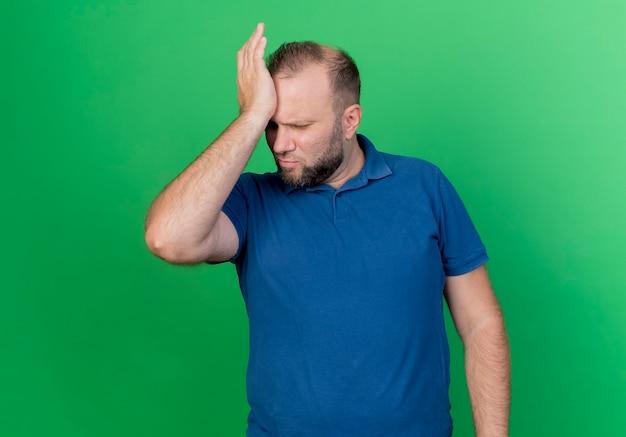 복사 공간이 녹색 벽에 고립 된 두통으로 고통을 내려다보고 머리에 손을 넣어 찡그림 성인 슬라브 남자