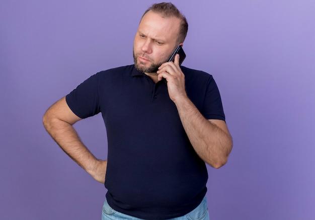 Accigliato uomo adulto slavo parlando al telefono guardando verso il basso tenendo la mano sulla vita isolata