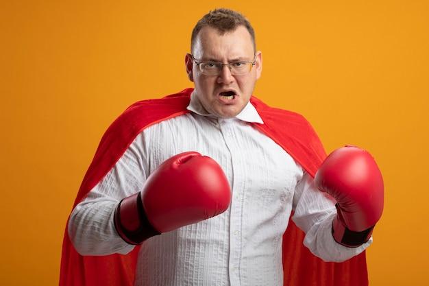 오렌지 벽에 고립 된 공기에 손을 유지 안경과 상자 장갑을 착용하는 빨간 케이프에서 성인 슬라브 슈퍼 히어로 남자를 찡그림