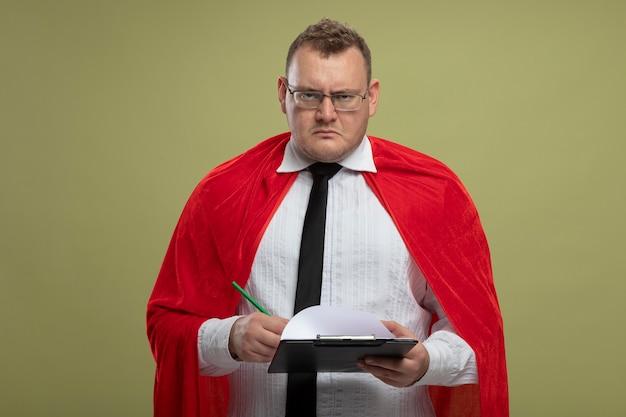 コピースペースでオリーブグリーンの壁に隔離された眼鏡とネクタイ保持ペンとクリップボードを身に着けている赤いマントで眉をひそめている大人のスラブのスーパーヒーローの男