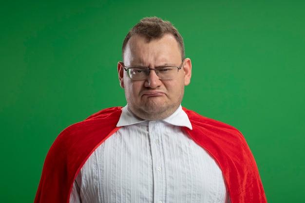 Accigliato uomo adulto supereroe slavo in mantello rosso con gli occhiali isolati sulla parete verde
