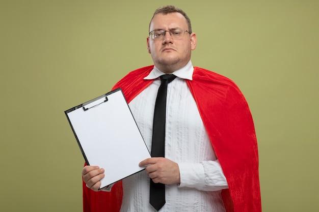 Accigliato uomo adulto supereroe slavo in mantello rosso con gli occhiali e cravatta che tiene appunti isolato sulla parete verde oliva