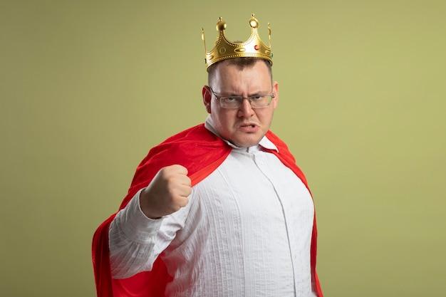 올리브 녹색 벽에 고립 된 전면 떨림 주먹을보고 안경과 왕관을 쓰고 빨간 케이프에서 찡그림 성인 슈퍼 히어로 남자