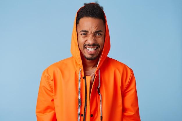 Il ragazzo afroamericano accigliato indossa un cappotto impermeabile arancione che fa smorfie, sente un terribile mal di testa che è insopportabile da sopportare, sembra arrabbiato in piedi.