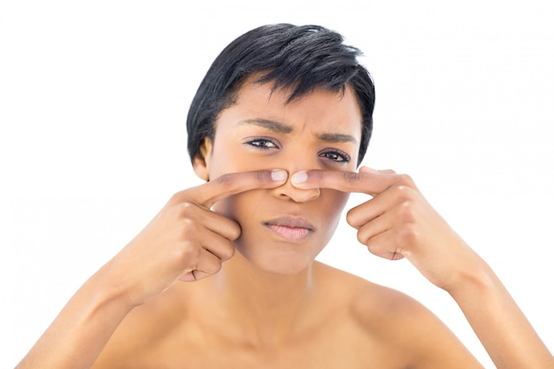 Frowning black haired woman popping a pimple