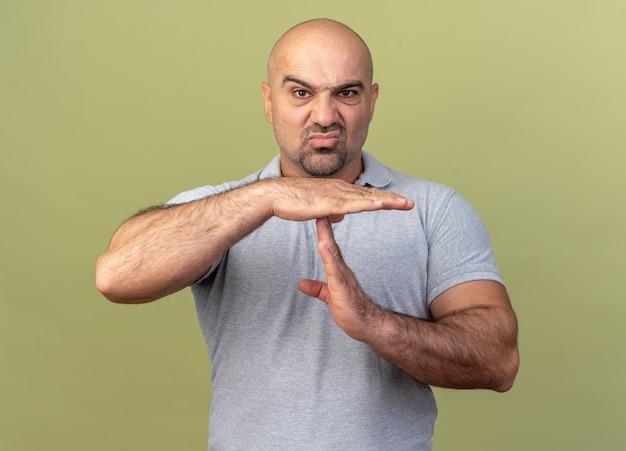 Хмурый случайный мужчина средних лет, смотрящий вперед, делает жест тайм-аута, изолированный на оливково-зеленой стене